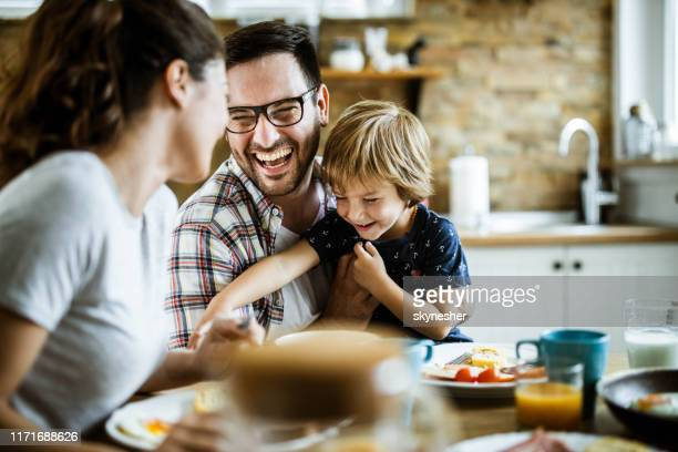 young cheerful family having fun at dining table. - espontânea imagens e fotografias de stock