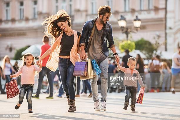 young cheerful family running with shopping bags on the street. - gezin met twee kinderen stockfoto's en -beelden