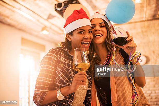 Young cheerful female colleagues at New Year's office party.