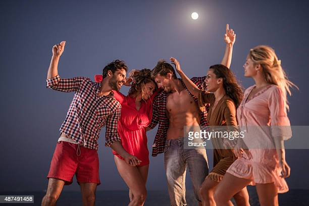 Young cheerful friends dancing on a beach party at night.
