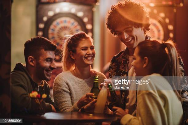 young cheerful friends toasting after playing darts in a bar. - dart stock pictures, royalty-free photos & images