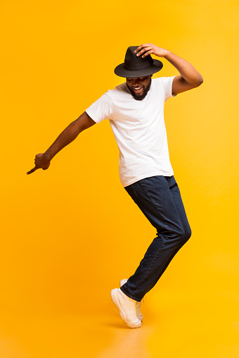 Young cheerful man dancing on tiptoes on yellow studio background 1172135938