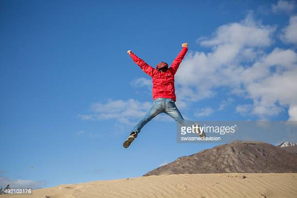 Young cheerful man in desert jumping makes cross shape