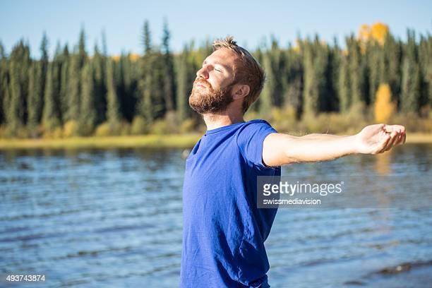 Jeune gai homme détente au bord du lac, les bras tendus