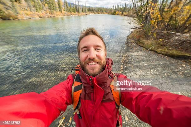 Jeune gai homme voyage dure une autophoto portrait près de la rivière