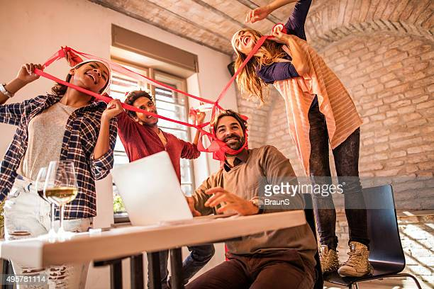 Young cheerful people celebrating New Year around busy businessman.