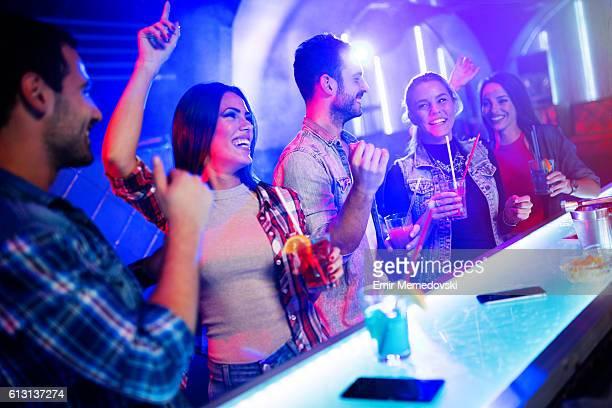 Young cheerful people having fun in nightclub.