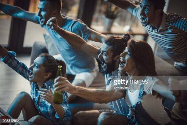 Young cheerful people having fun while cheering for their favorite sports team at home.