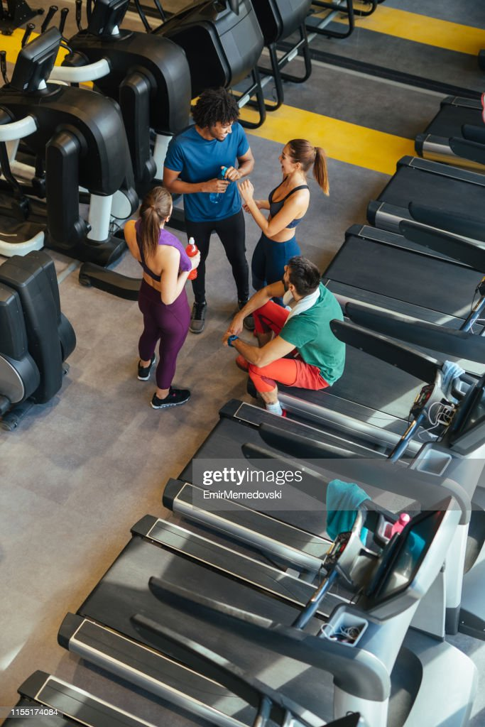 Young cheerful people resting from exercising at gym and communicating : Stock Photo
