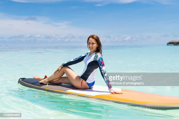 young cheerful surfer woman in swimwear on the beach in maldives ready to enoy the ocean waves, real people, luxury tourist resort, beach vacation, water sport, leisure activity, maldives beach, beach holiday, slim fit 20-25 years old caucasian supsurf - この撮影のクリップをもっと見る 2025 stock pictures, royalty-free photos & images