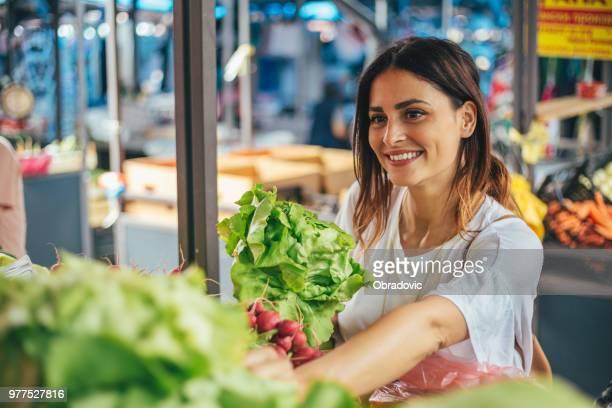 Junge fröhliche Frau auf dem Markt
