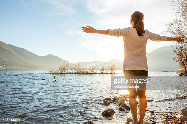 Young cheerful woman by the lake enjoying nature