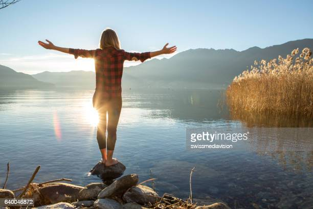 young cheerful woman by the lake enjoying nature - alternatieve geneeswijzen stockfoto's en -beelden