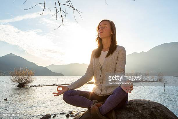 Young cheerful woman by the lake exercising yoga at sunrise