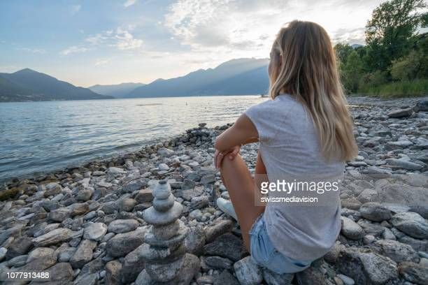 young cheerful woman by the lake watching the sunset, stack rocks beside - ascona stock photos and pictures