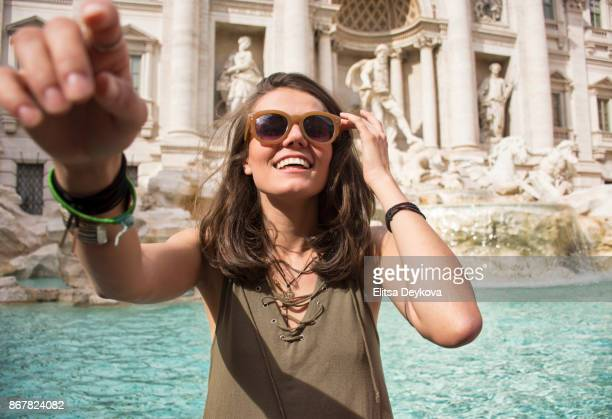 young cheerful woman having fun in front of trevi fountain - trevi fountain stock photos and pictures