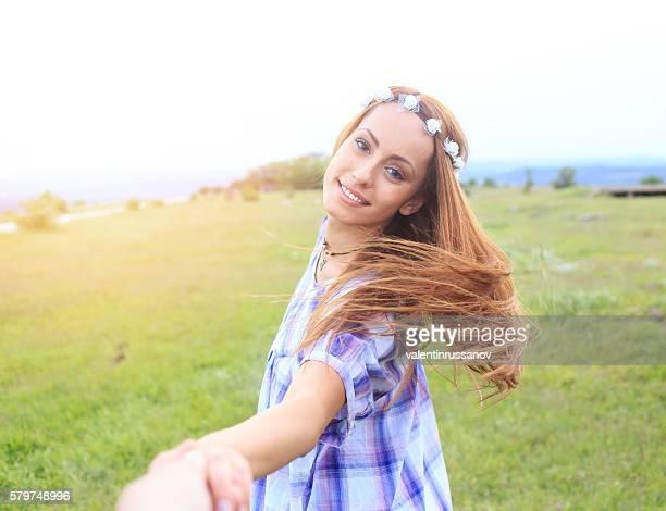 Young cheerful woman having fun on grassland