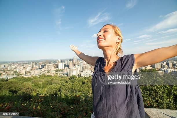 Gaie jeune femme à Montréal, au Canada, les bras tendus pour Expression positive