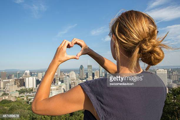 Young cheerful woman in Montreal-Canada making heart shape with hands
