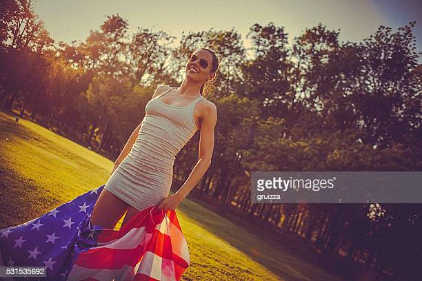 Young cheerful woman standing in a meadow holding american flag
