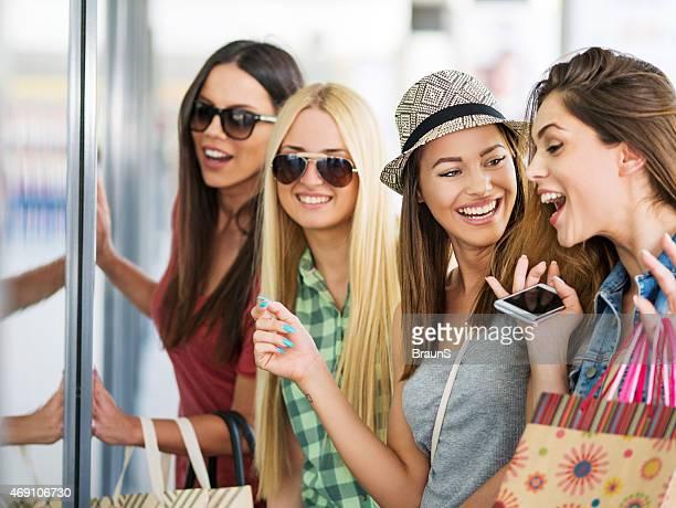 Young cheerful women having fun while window shopping.