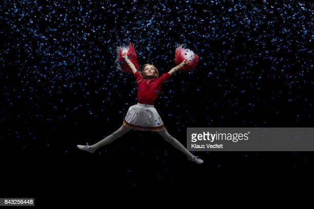 young cheerleader girl with pom poms, jumping in room with blue confetti - cheerleader up skirt stock photos and pictures