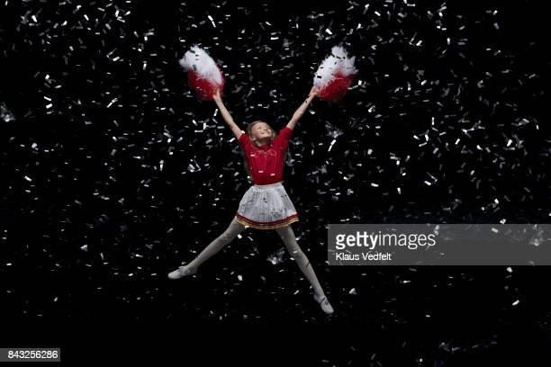 young cheerleader girl with pom poms, jumping in room with confetti - cheerleader up skirt stock photos and pictures