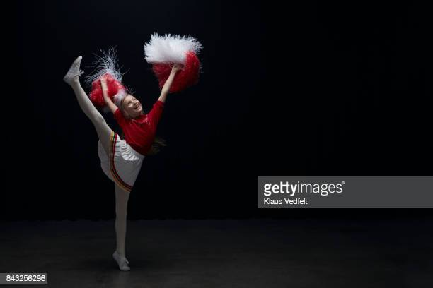young cheerleader girl with pom poms, jumping with leg stretched - cheerleader high kick stock photos and pictures