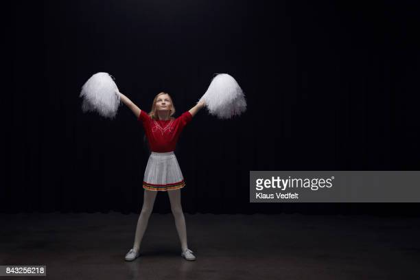 Young cheerleader girl with pom poms, looking devoted into the light