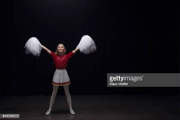 Young cheerleader girl with pom poms, looking in camera