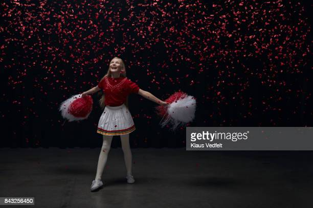 young cheerleader girl with pom poms looking up at red confetti falling down - cheerleader up skirt stock photos and pictures