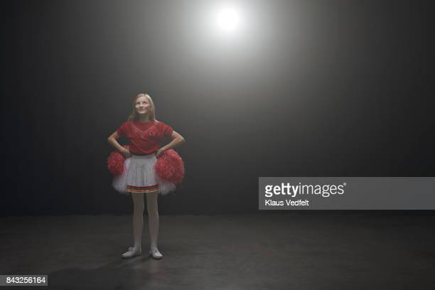 Young cheerleader girl with pom poms, looking up in the light