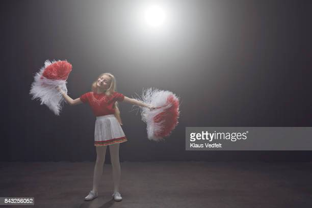 Young cheerleader girl with pom poms smiling with closed eyes