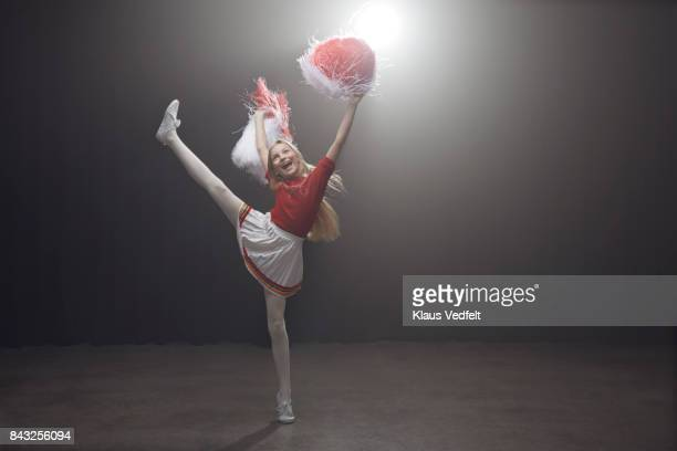 young cheerleader girl with pom poms, standing on one leg - cheerleader high kick stock photos and pictures