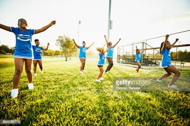 young cheerleaders practicing routine in park during early morning workout - black cheerleaders stock photos and pictures