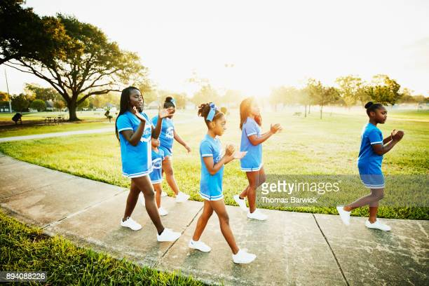 Young cheerleaders walking together to early morning practice in park
