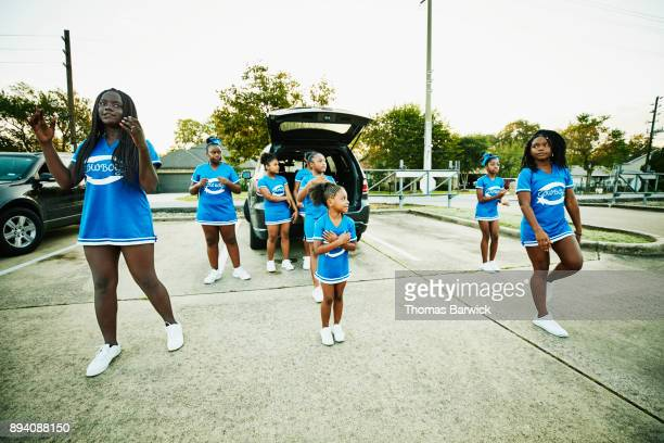 young cheerleaders warming up together in parking lot - black cheerleaders stock photos and pictures