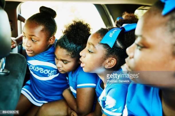 Young cheerleading teammates sitting in back seat of car on way to practice