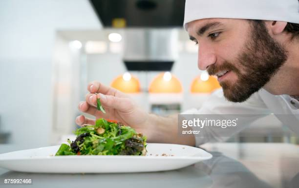 Young chef adding details to an appetizer he just made