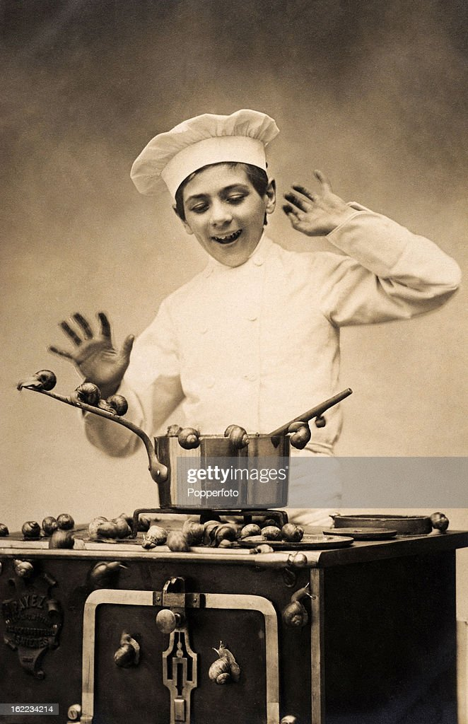 A young chef alarmed by reluctant snails, circa 1920.