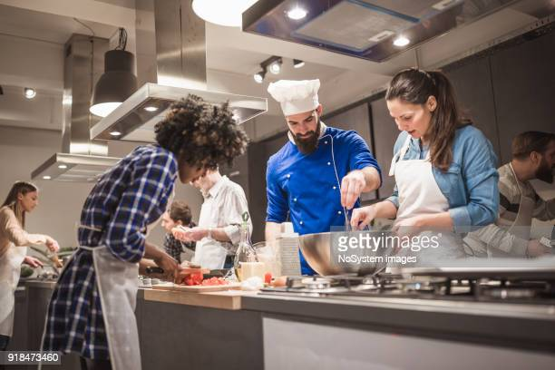 young chef assisting a cooking class and explaining some tips and tricks - food and drink stock pictures, royalty-free photos & images