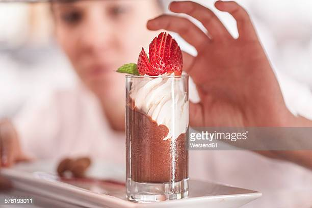 Young chef finishing chocolate dessert