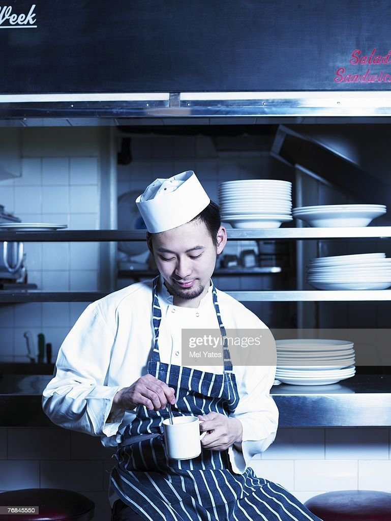 Young Chef Taking Break In Kitchen Holding Cup Smiling Stock Photo ...