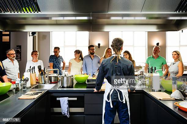 Young chef welcoming his cooking class
