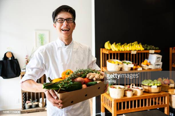 young chef with a box full of organic groceries - homegrown produce stock pictures, royalty-free photos & images