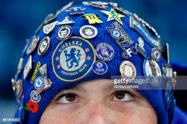 TOPSHOT A young Chelsea fan wearing a badgecovered hat waits for kick off in the English Premier League football match between Chelsea and Swansea...