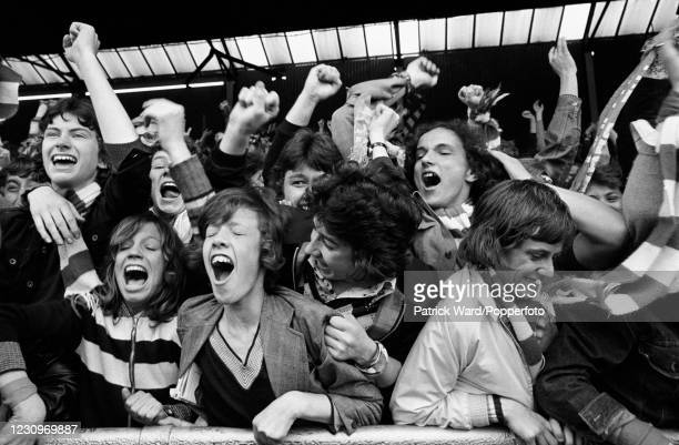 """Young Chelsea football fans in the """"Shed"""" celebrate their team scoring a goal, London, circa 1975. This image is from a series of social documentary..."""