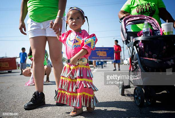 A young Cheyenne/Arapaho jingle dancer walks the parade route of the Red Earth Native American Festival Friday June 10 2016 in Oklahoma City