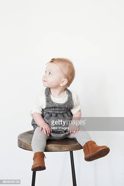 A young child, a girl sitting on a tall stool.