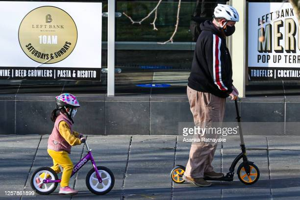 Young child and man wearing masks are seen riding a bicycle and scooter respectively in Southbank on July 24, 2020 in Melbourne, Australia. Face...